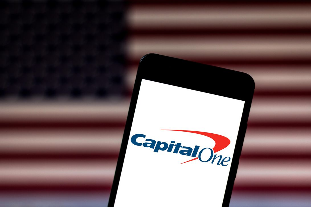 The Capital One logo is visible on a phone screen with the American flag in the background.