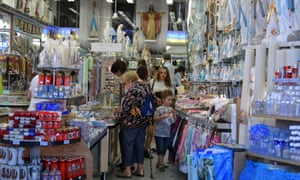 Catholic pilgrims visit a gift shop in Lourdes