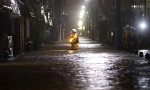 A firefighter makes his way through a flooded residential street in in Tokyo