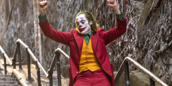 Joaquin Phoenix in makeup Joker arms raised on stairs