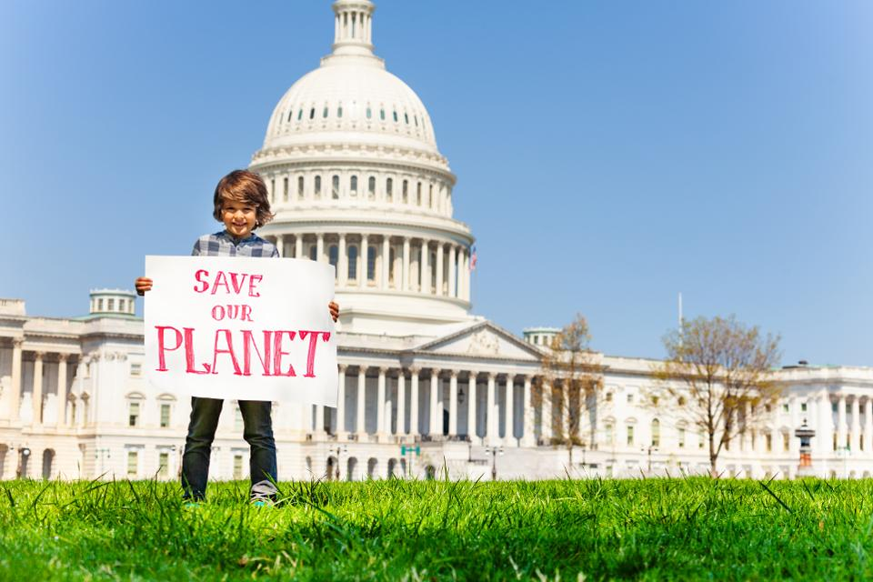 Protester holding sign save our planet in hands