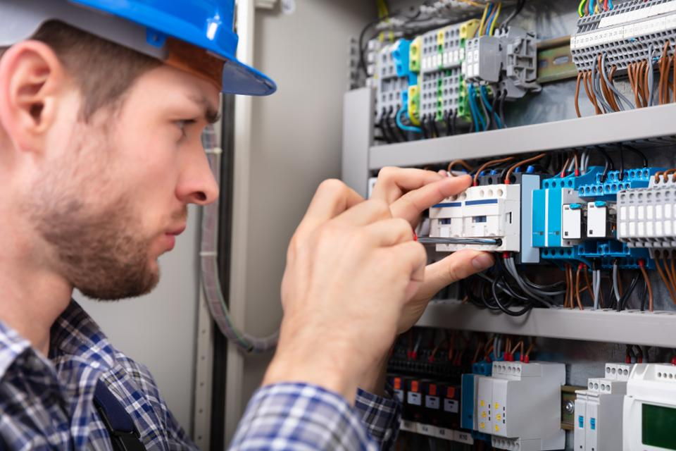 Technician Repairing Fuse Box With Screwdriver