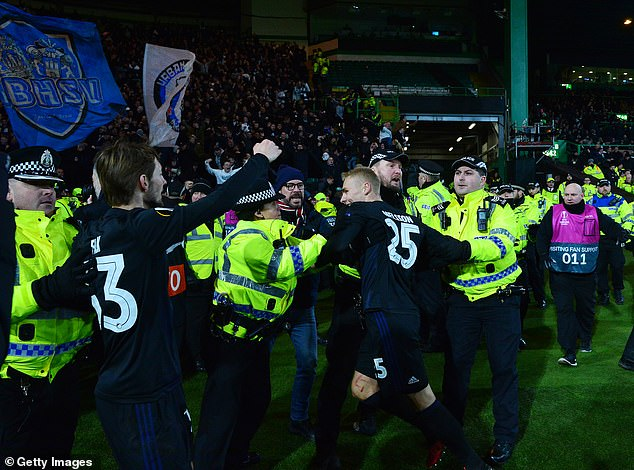 Officers attempt to restrain the Copenhagen players as they try to celebrate with their fans