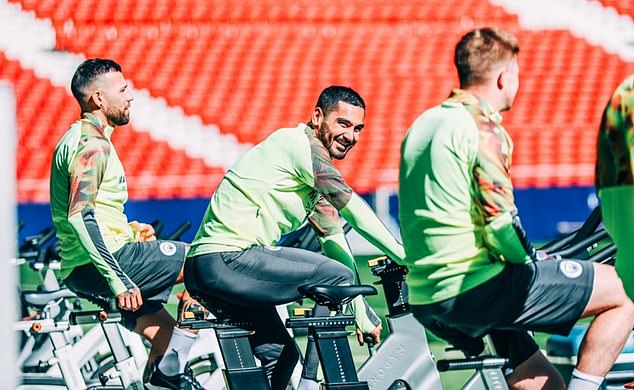 City midfielder Ilkay Gundogan smiles for the camera as he cycles on an exercise bike