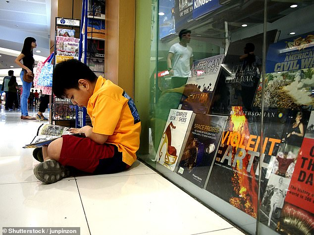 Researchers found that children who read books on a daily basis achieved higher test results on average, equivalent to having had three additional months of secondary school education under their belts. However, the team found that reading newspapers, comics, magazines or even short stories did not have the same benefit. Pictured, a child reading a comic book