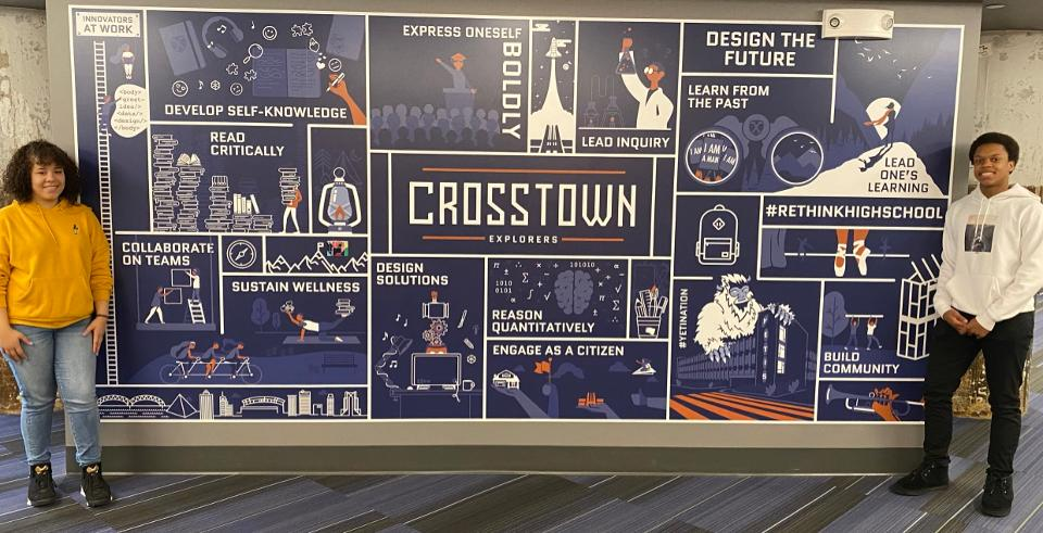 Students stand on either side of a poster of the 12 Crosstown High Competencies