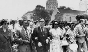 In May 1970, United Auto Workers president Leonard Woodcock, in glasses and dark suit, locks arms with Coretta Scott King and Joseph E Lowery as they lead a protest march in Atlanta.