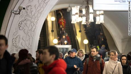 In this photo taken on  Feb. 22, a surveillance camera, top left, is seen as people walk down in a Moscow's Metro.