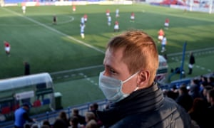 A fan wears a protective mask as he watches FC Minsk's latest match.