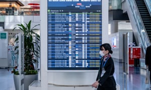 A woman walks past the flight notice board wearing a face mask as a preventive measure, during the coronavirus pandemic on 28 March, 2020 in Tokyo, Japan.
