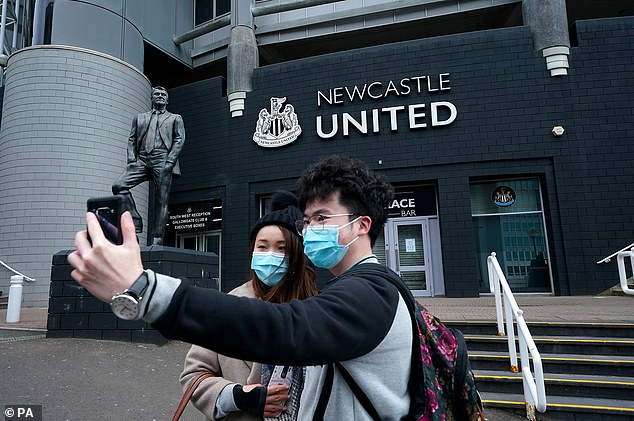 Two mask-wearing fans pose for a selfie outside Newcastle United's St James' Park